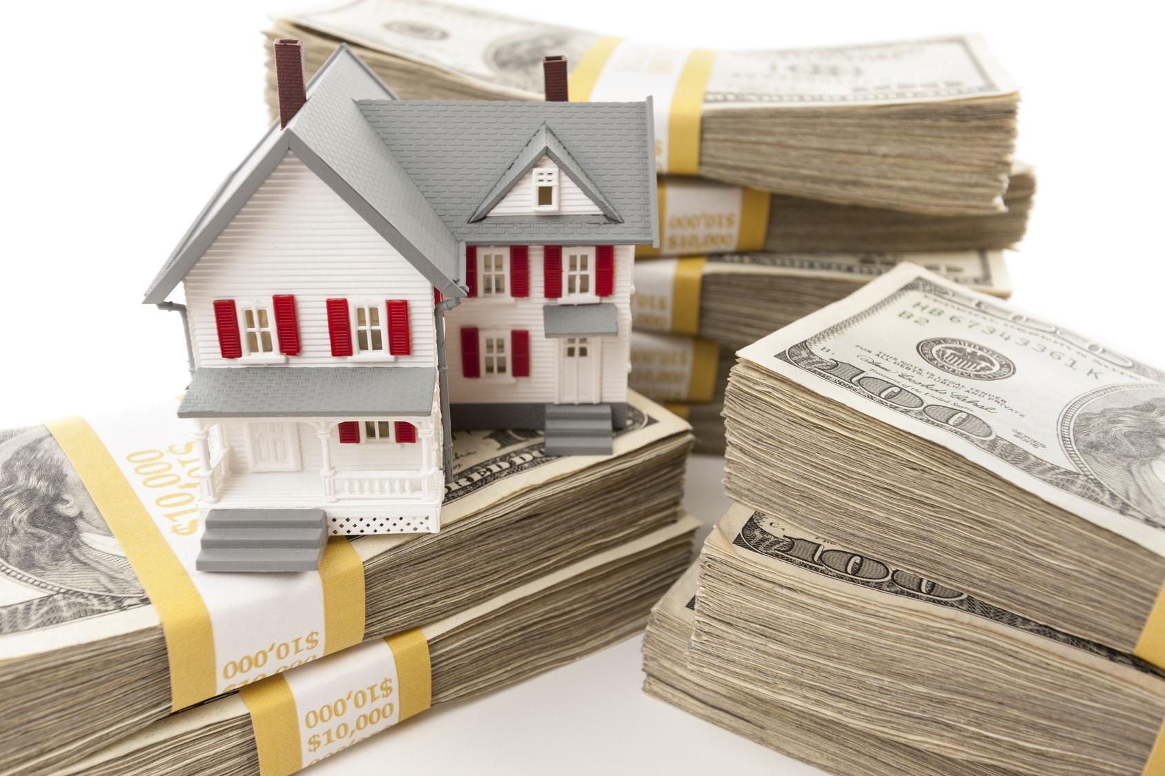 Stacks of one hundred dollar bills with small house for Acheter une maison en floride